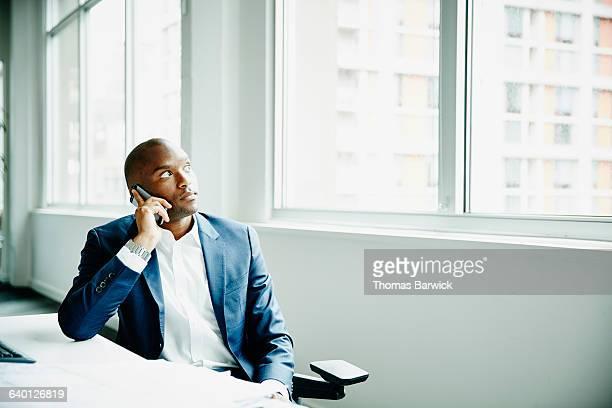 Businessman on smartphone sitting at office desk