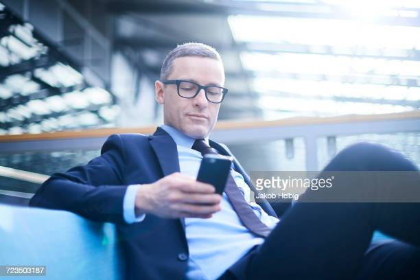 businessman on sofa looking at smartphone in office atrium - costume complet photos et images de collection