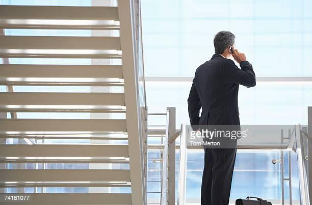 Homme d'affaires sur l'escalier avec téléphone portable