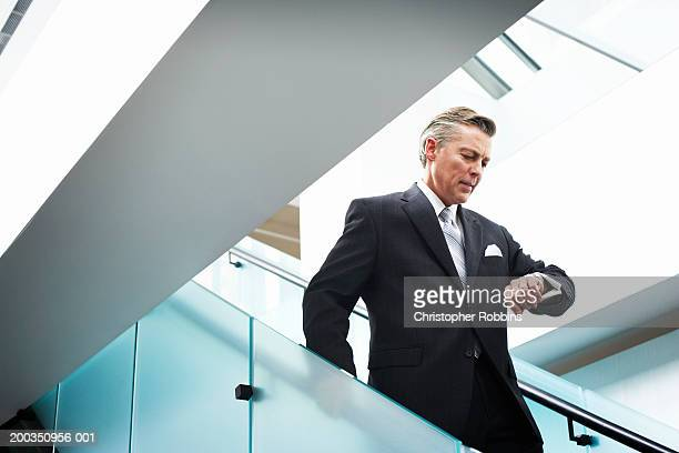 Businessman on stairs, looking at watch, low angle view