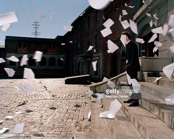 Businessman on steps, papers flying in wind (blurred motion)