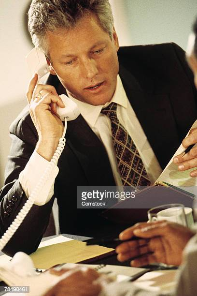 Businessman on telephone in busy office