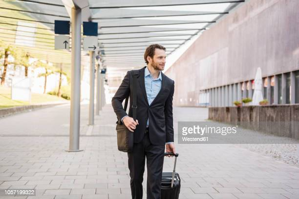 Businessman on the move pushing rolling suitcase