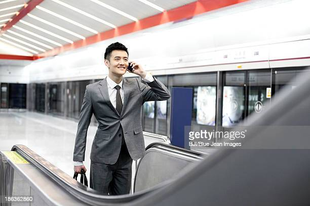 Businessman on the phone and taking escalator at subway station