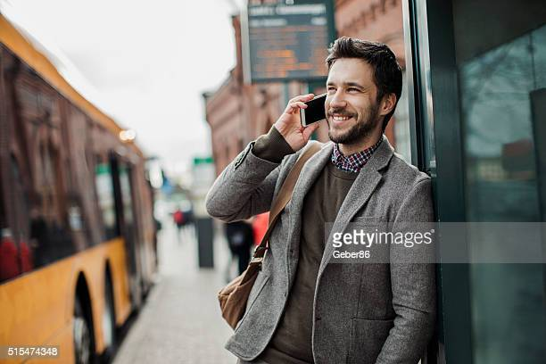 Businessman on the phone at bus station