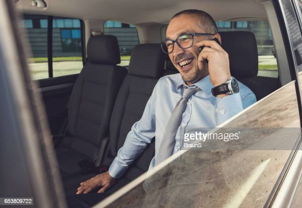 Businessman on the phone at the back seat of car.