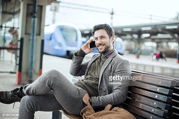 Businessman on the phone at train station