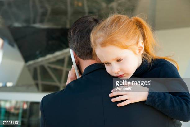 Businessman on the phone holding daughter
