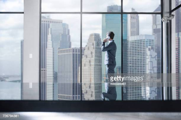 Businessman on the phone in city office looking out of window