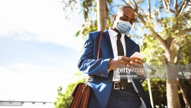 zakenman op de telefoon in miami tijdens lockdown - zwart pak stockfoto's en -beelden
