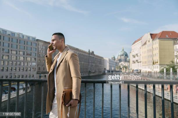 businessman on the phone standing on a bridge, berlin, germany - ベルリン王宮 ストックフォトと画像