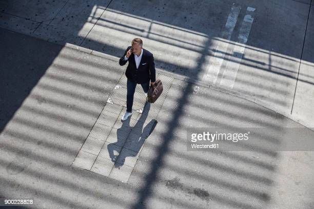 businessman on the phone walking on pavement, top view - zugänglichkeit stock-fotos und bilder
