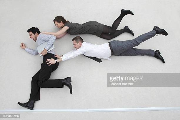 businessman on the run, two colleagues after him, flying in the air, side view - homem pegando mulher imagens e fotografias de stock