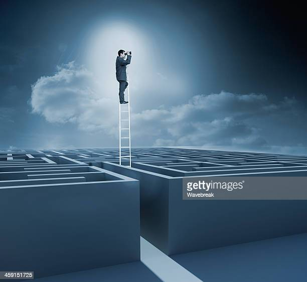 Businessman on top of a ladder in maze during night