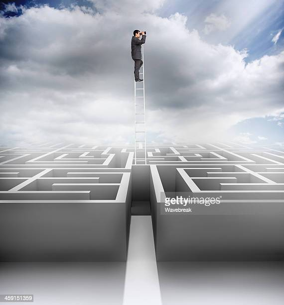 Businessman on top of a ladder looking for exit