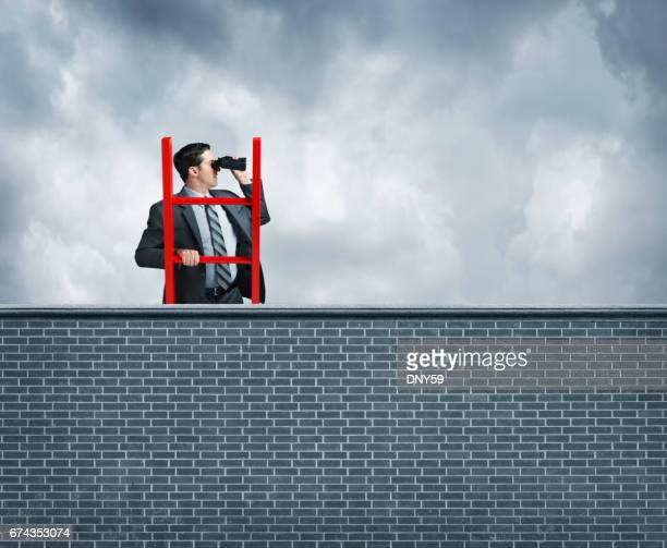 Businessman On Top Of Ladder Looks Over Wall With Binoculars