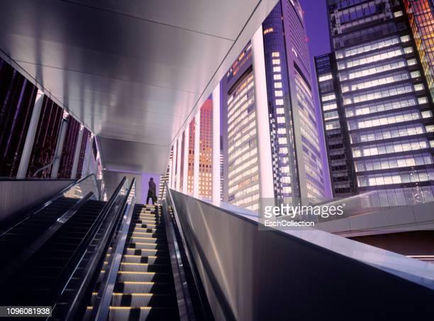businessman on top of moving escalator at modern illuminated business district - 金融と経済 ストックフォトと画像