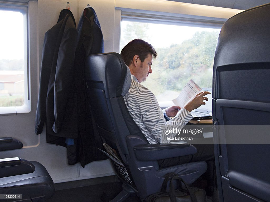 Businessman on train reads paperwork : ストックフォト
