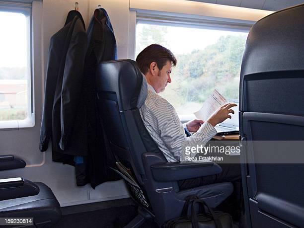 Businessman on train reads paperwork