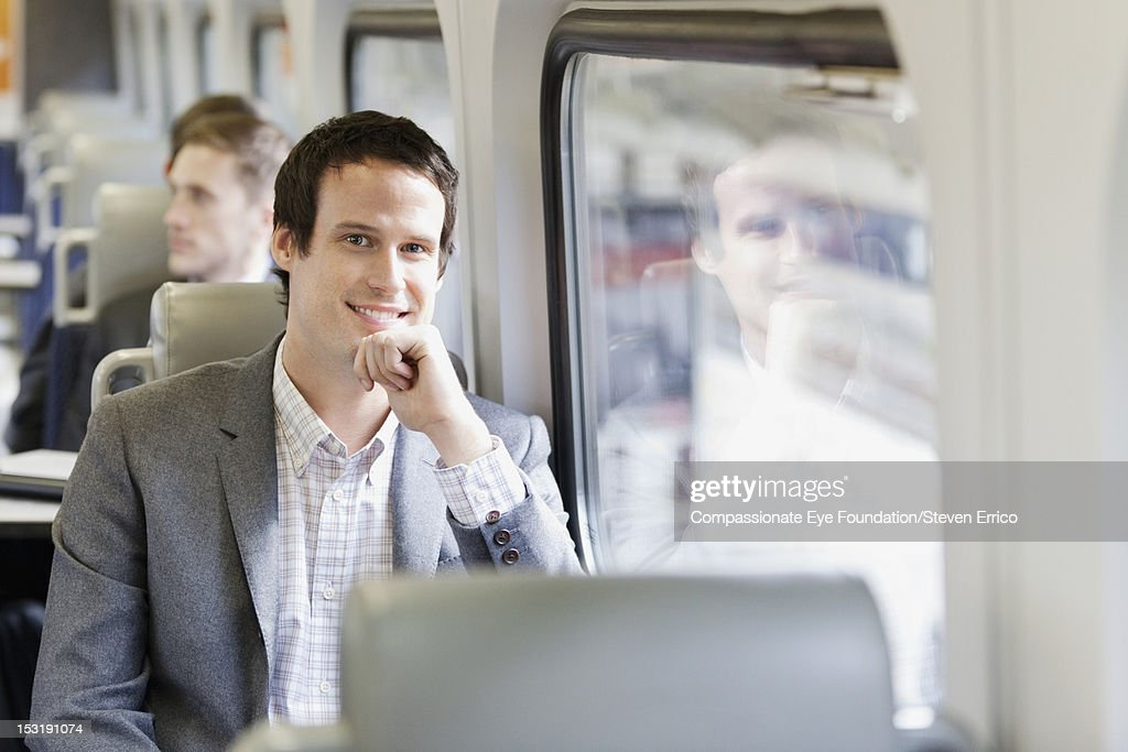 Businessman on train, smiling : Stock Photo