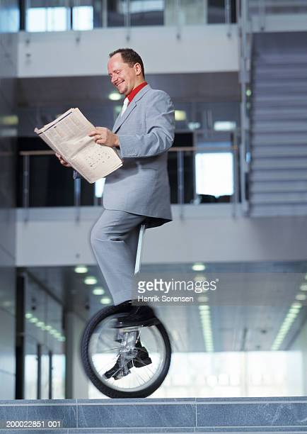 Businessman on unicycle reading newspaper