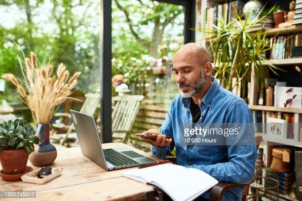 businessman on video conference using speakerphone at home - one mature man only stock pictures, royalty-free photos & images