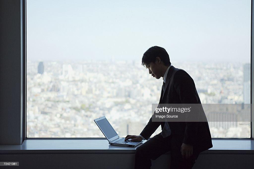 Businessman on window ledge with laptop : Stock Photo