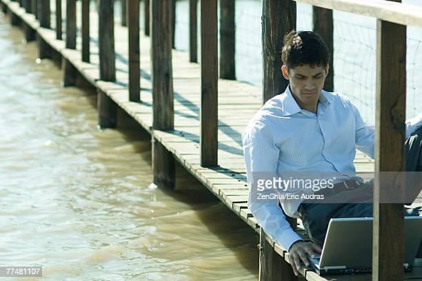 Businessman on wooden footbridge over lake, using laptop