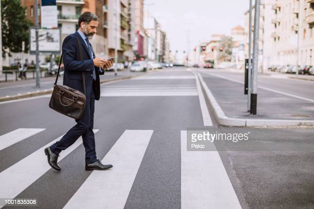 businessman on zebra crossing - pedestrian crossing stock photos and pictures