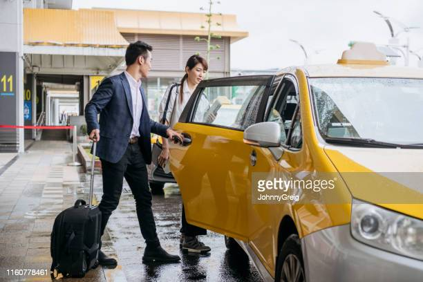 businessman opening cab door for woman outside airport - charming stock pictures, royalty-free photos & images