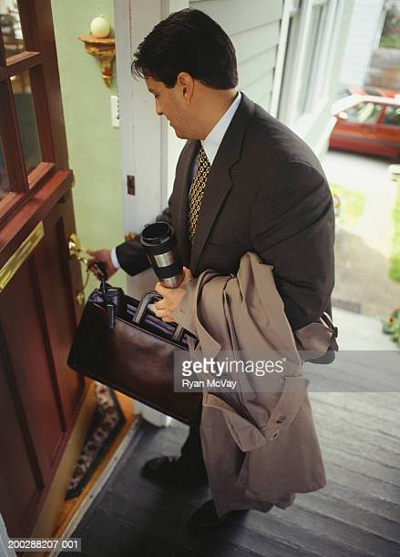 Businessman opening front door to house