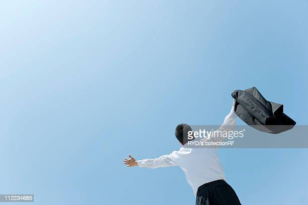 A businessman opening hands up to the sky