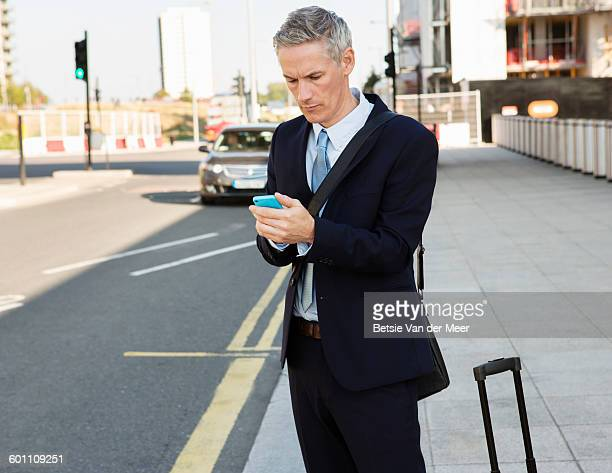 Businessman orders cab,by using apps in street.