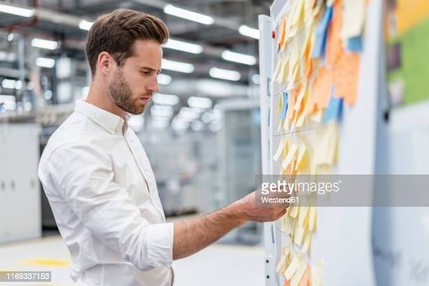 businessman organizing adhesive notes on a board in a factory - brainstorming stock pictures, royalty-free photos & images
