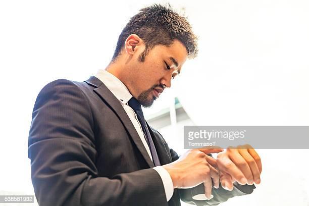 実業家屋外のチェック彼のスマートをご覧いただけます。