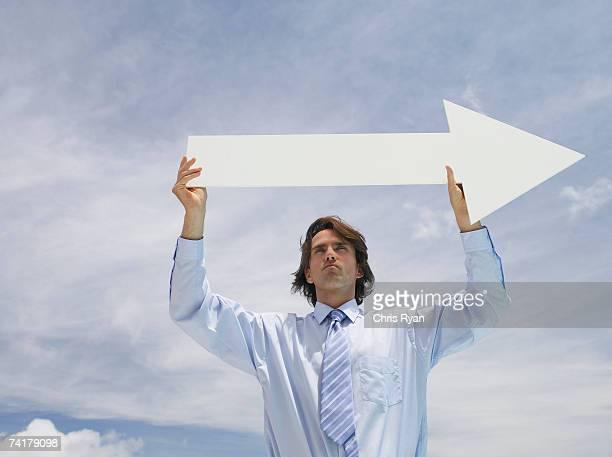 Geschäftsmann im Freien holding leere Pfeil mit Himmel im Hintergrund.