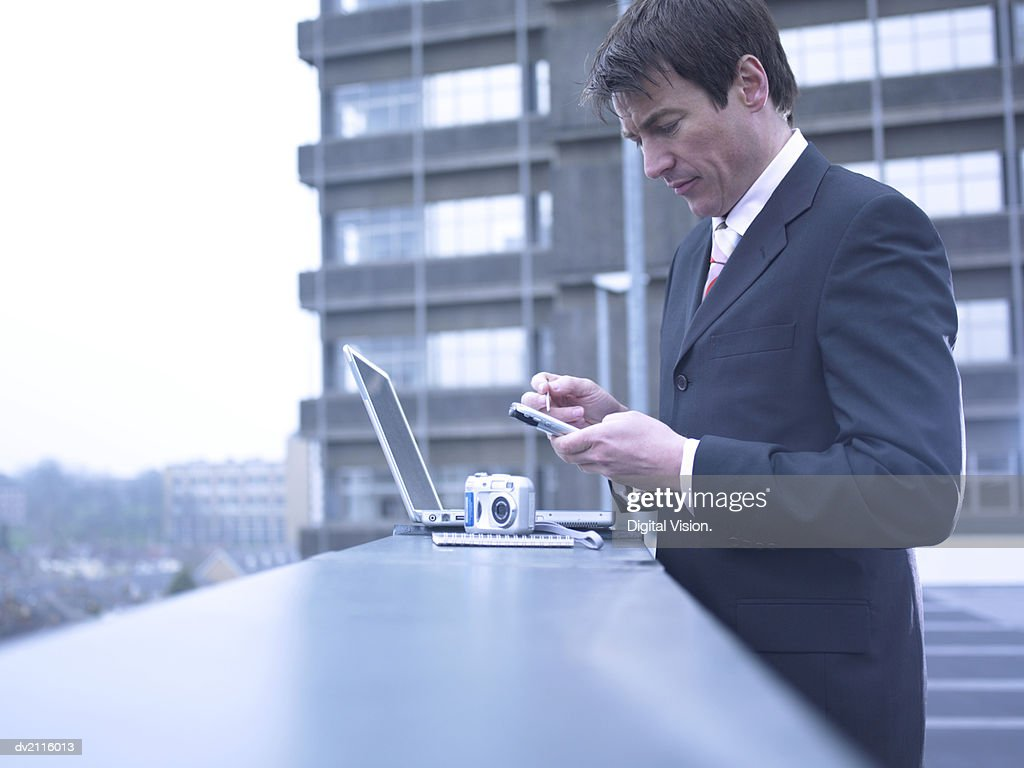 Businessman Outdoors in the City Using a Handheld PC : Stock Photo