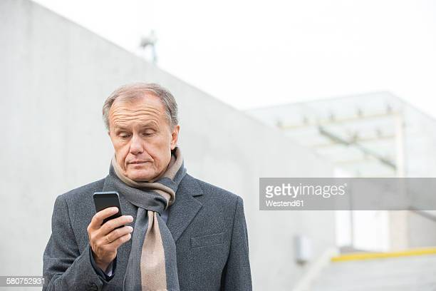 Businessman outdoors looking at cell phone