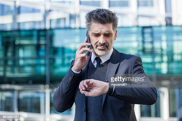 Businessman outdoors on cell phone checking the time