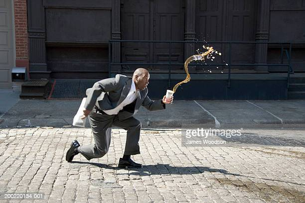 businessman outdoors, spilling cup of coffee on pavement, side view - kaffee getränk stock-fotos und bilder