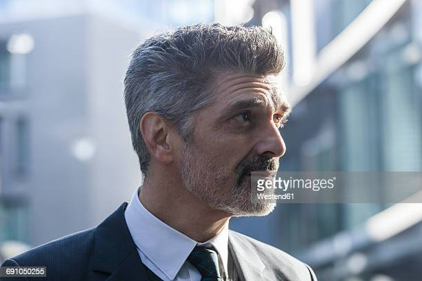 Businessman outdoors thinking