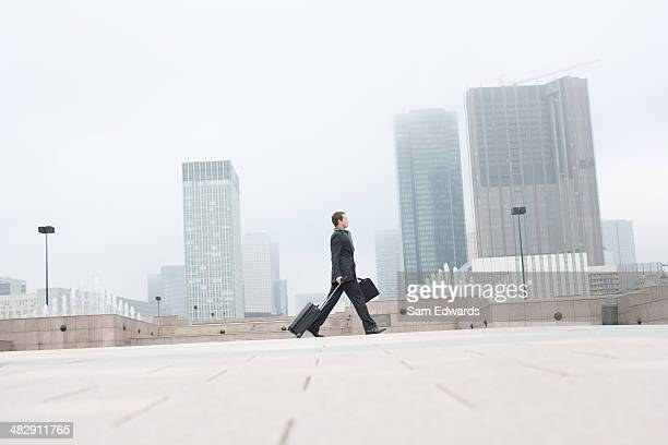 Geschäftsmann im Freien mit Gepäck zu Fuß