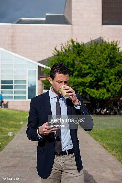 Businessman outdoors with cell phone and coffee to go