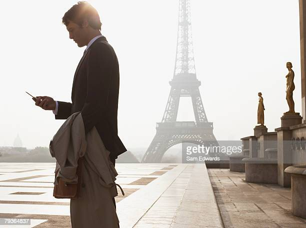 Businessman outdoors with cellular phone by Eiffel Tower