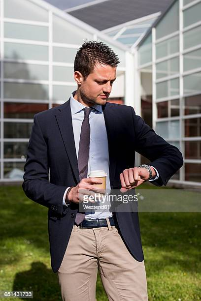 Businessman outdoors with coffee to go checking the time