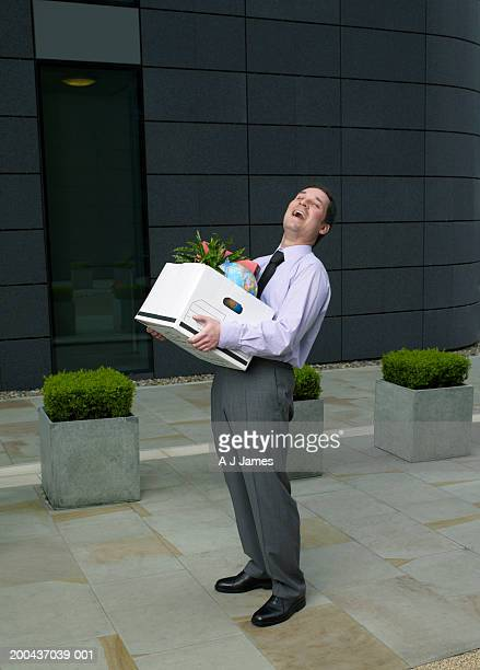 Geschäftsmann außerhalb Gebäude holding Karton von Gegenständen, Lachen