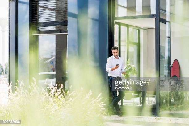 businessman outside office building looking at cell phone - fensterfront stock-fotos und bilder
