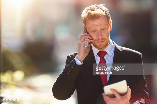 Businessman outside on phone looking at iPad