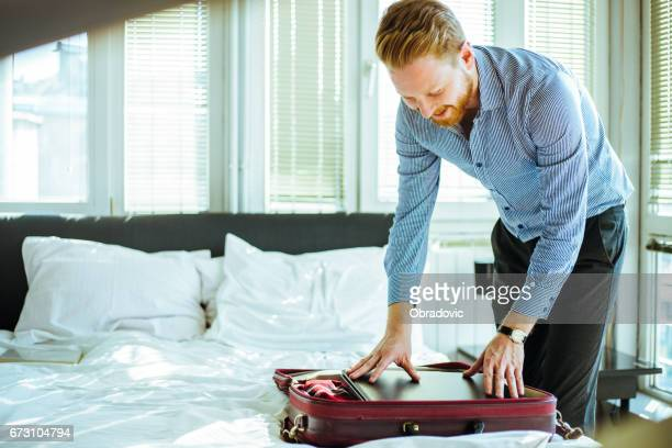 Businessman packing laptopt in the suitcase
