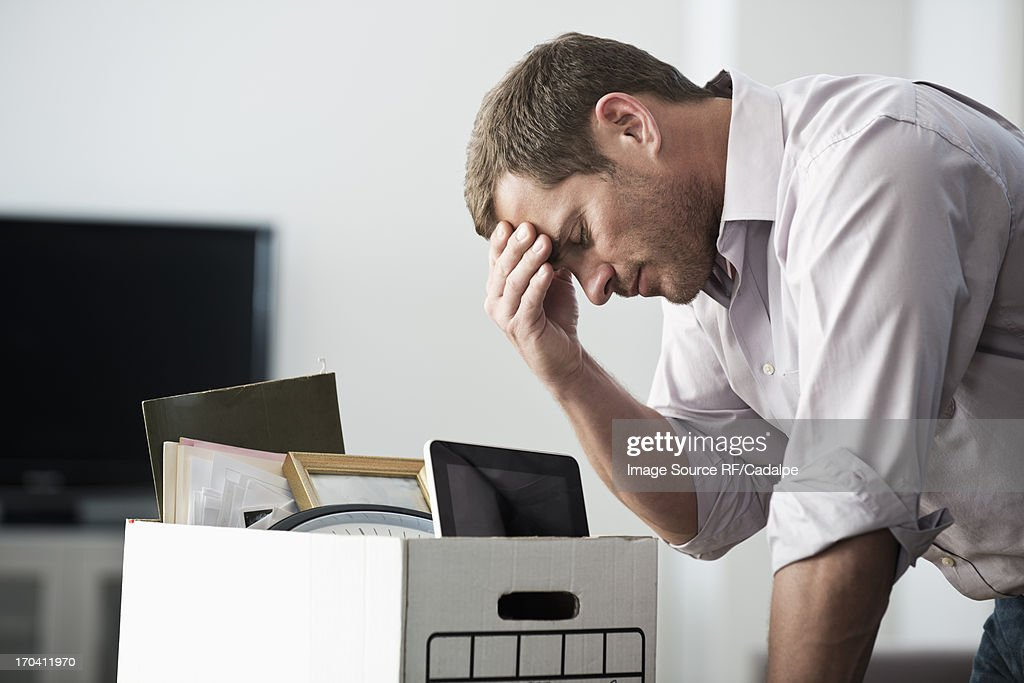Businessman packing up box in office : Stock Photo